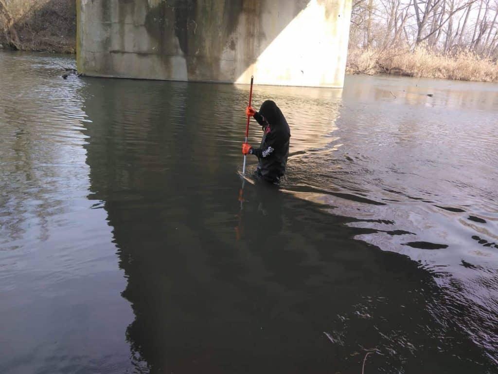Lovec ve vodě používá magnet připevněný na tyči