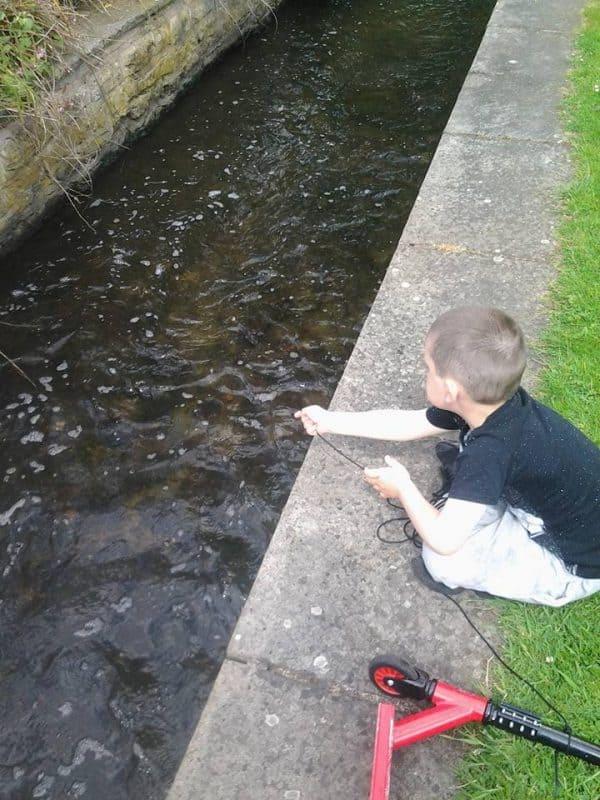 dítě hledá poklady v místním potoce